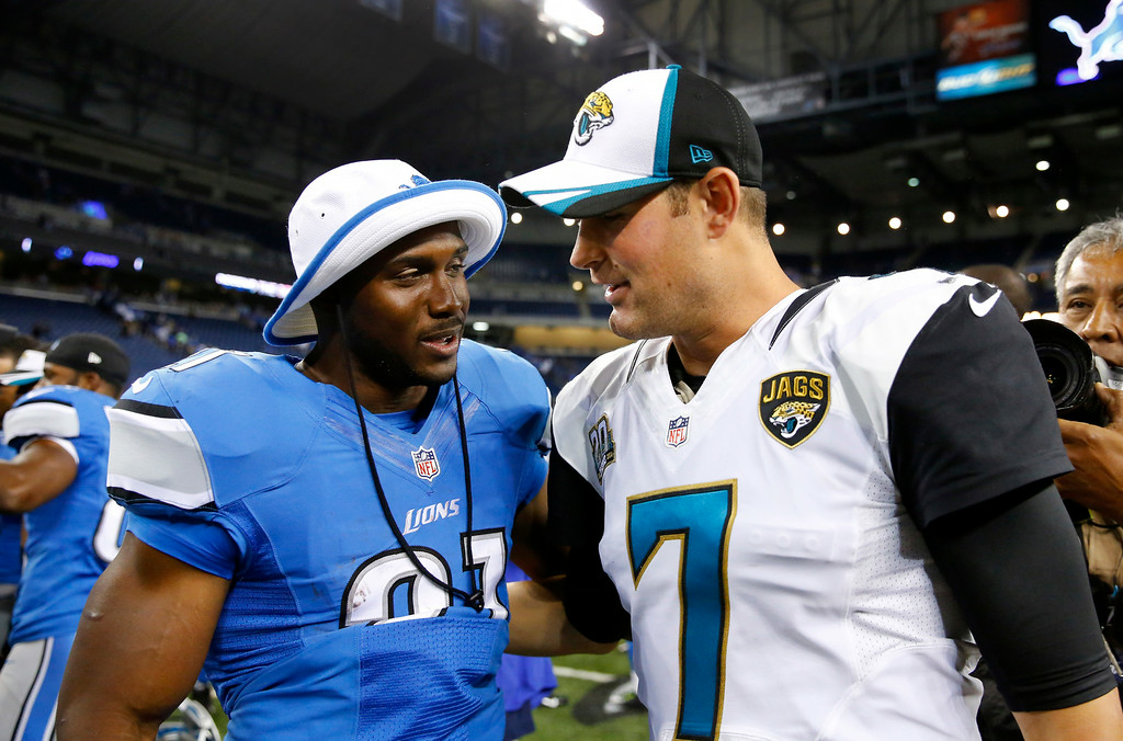 . Detroit Lions running back Reggie Bush, left, talks with Jacksonville Jaguars quarterback Chad Henne (7) after a preseason NFL football game at Ford Field in Detroit, Friday, Aug. 22, 2014. (AP Photo/Rick Osentoski)