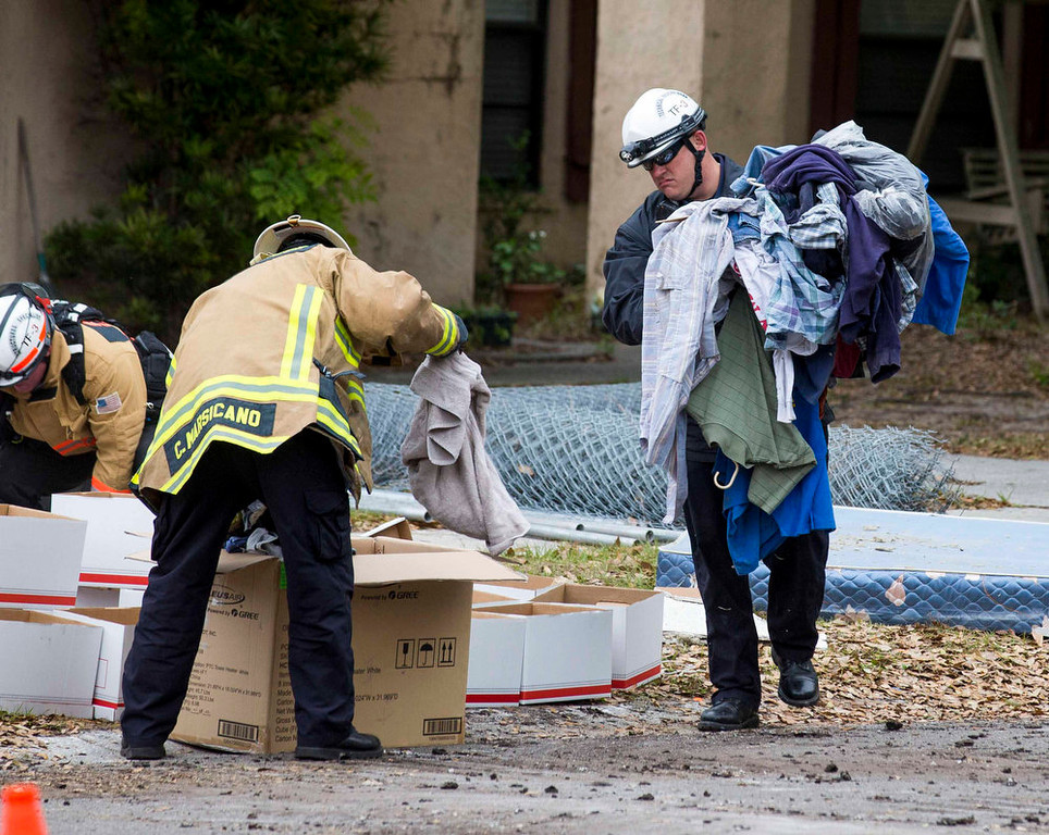 . Hillsborough County firefighters help salvage family belongings from the home, where Jeffrey Bush was swallowed by a sinkhole, during its demolition in Seffner, Florida March 3, 2013. Florida rescue workers ended their efforts on Saturday to recover the body of Jeffrey Bush, who disappeared into the sinkhole that swallowed his bedroom while he slept and demolished the suburban Tampa home due to its dangerous conditions, a rescue spokeswoman said.  REUTERS/Scott Audette