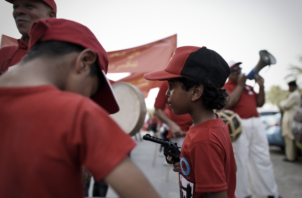 . A Bahraini boy holds a toy pistol during a May Day rally on May 1, 2014 in Isa Town, south of Manama. (MOHAMMED AL-SHAIKH/AFP/Getty Images)