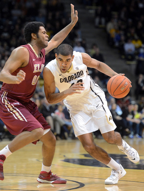 . Josh Scott of CU drives on Brian Dawkins of Elon during the first half of the December 13, 2013 game in Boulder. (Cliff Grassmick/Boulder Daily Camera)