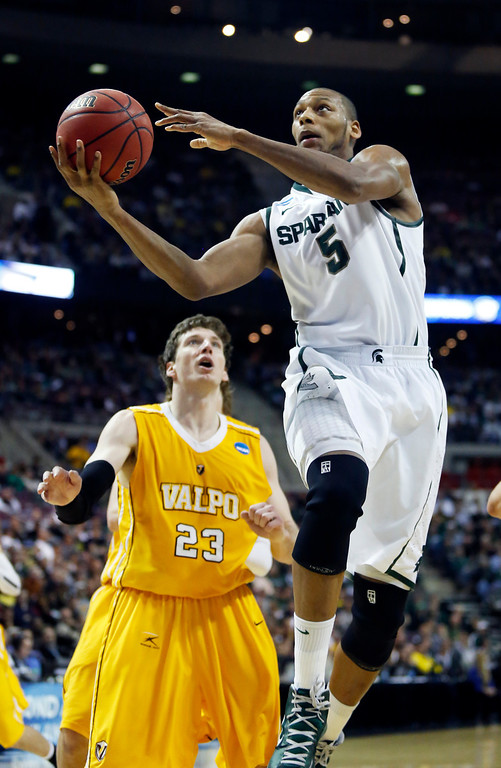 . Michigan State forward Adreian Payne (5) goes to the basket past Valparaiso guard Matt Kenney (23) in the first half of a second-round game of the NCAA college basketball tournament Thursday, March 21, 2013, in Auburn Hills, Mich. (AP Photo/Duane Burleson)