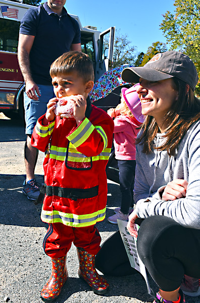 Hey Firefighters eat donuts too, right, so says Bennett Mutnansky 3, there along with his mom Jessica Mutnansky both from Chelmsford and at the Tyngsboro Fire Dept Open House. SUN/David H.Brow