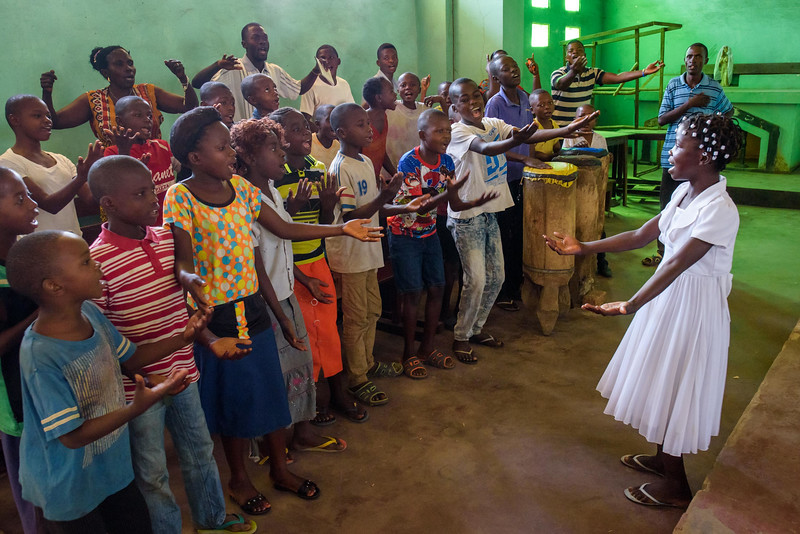 """Kapinga Alphoncine, 13 yr-old girl, leads choir practice at her church. She has a lovely voice! Her grandmother signs in the back row of the choir.  Kapinga lives with her widowed grandmother, Kapinga Godelive, 66 and her 3 brothers: 1-Francois Ngondo, 14 2-Mbuyamba Phillip, 9 3-Beya Honore, 6 Kananga, DRC Democratic Republic of Congo.  Worship Kapinga and her family go to the Catholic church nearby, Paroisse St. Therese Nganza. It's a large, Catholic church just behind Kapinga's house. Kapinga sings in the children's choir there. She loves to listen to Gospel songs, especially those with piano. She sings a little for us in high, clear voice. """"Mary the Mother of Jesus Christ. Mary has finished her mission by giving birth to someone who can give us salvation."""" We visited the church the next day to witness Kapinga's choir practice. About 20 young boys and girls sing with enthusiasm as a drummer pounds out a steady beat. Kapinga leads as their voices fill the cavernous church.   Inside Kapinga's four-room house the walls are paint splattered. There is little furniture except for two small tables and an old cabinet. On top sits a dusty old television. A peek behind reveals that it has no cord. Kapinga sits on a low, wooden bench against one wall reading an old school exercise book of English lessons. """"Good morning my friends, good morning.""""  Her English is good in spite of a mispronunciation here and there. High up on the wall to the right is a crucifix. It's as battle worn as the rest of the house. Light streams in through the numerous holes in the tin-sheeted roof. In the yard outside, the house is ringed on all sides with gardens of potato and cassava leaves, sorrel and sugarcane among other things.  In one corner of the yard a few visitors gather on homemade chairs under a thatched-roof patio. Across the compound the afternoon sun throws light on the smaller of the two buildings there. In chalk, just below the roof line are the words, """"Il n'ya pas de rose sans epine"""