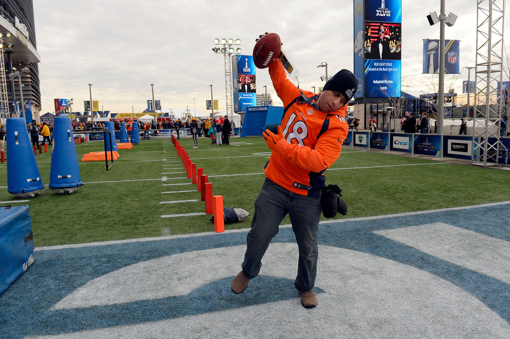 . Dave Browne of Belleville, NJ spikes the ball after scoreing a touchdown while playing a game for the fans outside of the stadium prior to the start of the game.  The Denver Broncos vs the Seattle Seahawks in Super Bowl XLVIII at MetLife Stadium in East Rutherford, New Jersey Sunday, February 2, 2014. (Photo by Craig Walker/The Denver Post)