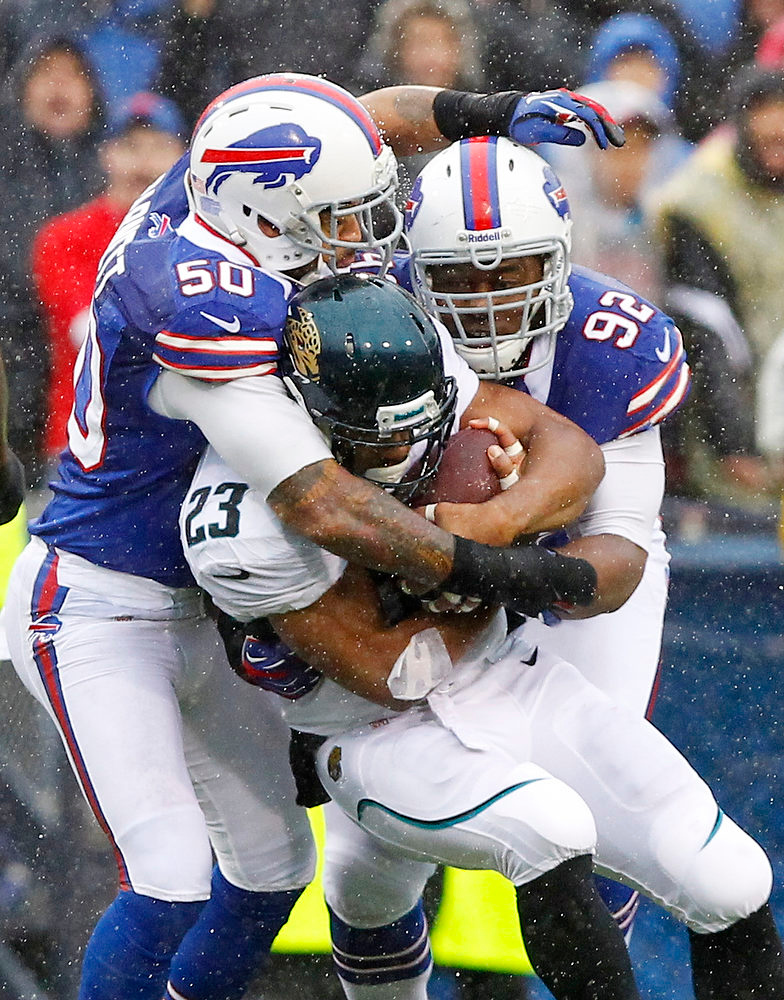 . Buffalo Bills\' Nick Barnett (50) and Alex Carrington (92) tackle Jacksonville Jaguars\' Rashad Jennings (23) during the first half of an NFL football game Sunday, Dec. 2, 2012 in Orchard Park, N.Y. (AP Photo/Bill Wippert)