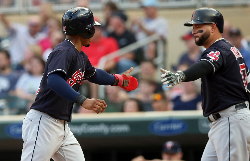 . Cleveland Indians\' Francisco Lindor, left, is congratulated by Yonder Alonso after Lindor scored on a double by Edwin Encarnacion off Minnesota Twins pitcher Jake Odorizzi during the first inning of a baseball game Thursday, May 31, 2018, in Minneapolis. Alonso went on to hit an RBI single. (AP Photo/Jim Mone)