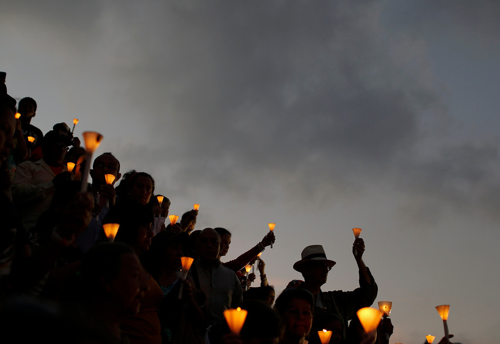 . People hold candles during a praying ceremony for the health of Venezuelan President Hugo Chavez in Caracas February 22, 2013. Venezuela\'s cancer-stricken president, Chavez, is still suffering respiratory problems after surgery in Cuba two months ago, the government said on Thursday in a sombre first communique since his homecoming this week. REUTERS/Jorge Silva