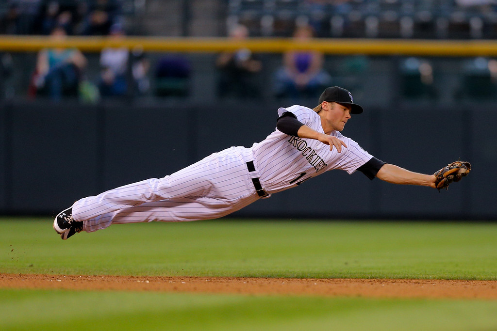 . DENVER, CO - SEPTEMBER 6:  Shortstop Josh Rutledge #14 of the Colorado Rockies makes a diving catch for the first out of the third inning against the San Diego Padres at Coors Field on September 6, 2014 in Denver, Colorado. (Photo by Justin Edmonds/Getty Images) *** BESTPIX ***