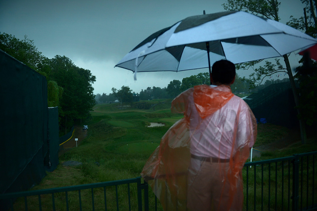 . A man looks out over the 18th hole after play was suspended during a storm at the first round the US Open at Merion Golf Club June 13, 2013 in Ardmore, Pennsylvania. AFP PHOTO/Brendan  SMIALOWSKI/AFP/Getty Images