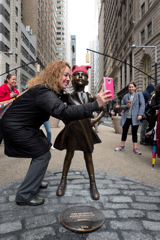 ". A woman takes a photo with a statue of a fearless girl, Wednesday, March 8, 2017, in New York. The statue was installed by an investment firm in honor of International Women\'s Day. An inscription at the base reads, ""Know the power of women in leadership. She makes a difference. State Street Global Advisors.\"" (AP Photo/Mark Lennihan)"
