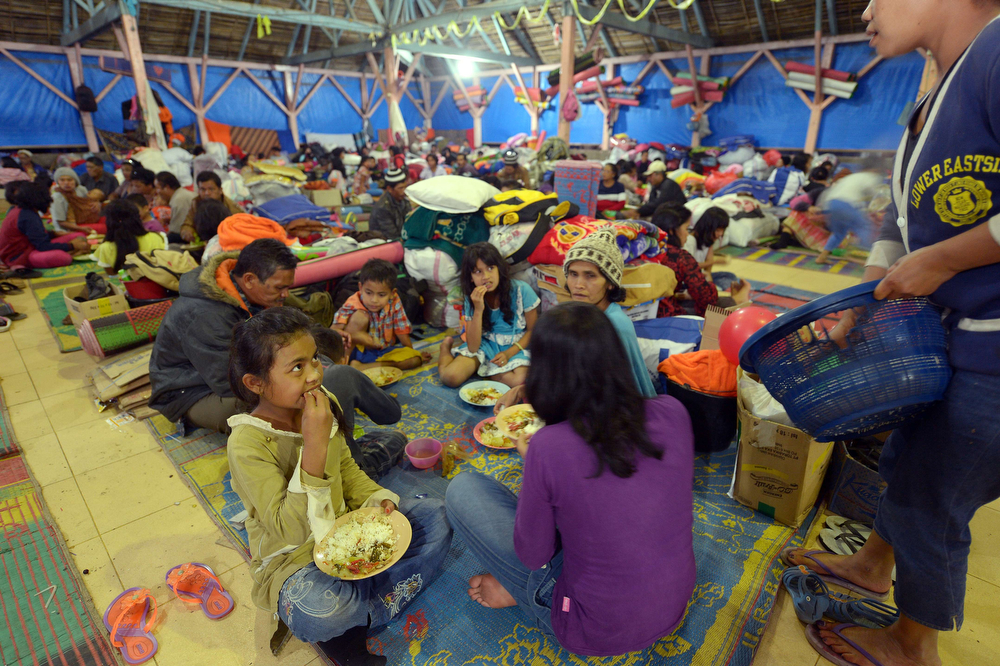 . Villagers have dinner at a temporary shelter in Karo on February 2, 2014 as they left their homes following Sinabung eruptions. Indonesian officials searched through thick ash for bodies on February 2 after Mount Sinabung volcano erupted, killing at least 15 people, with the only sign of life an ownerless mobile phone ringing inside an abandoned bag. (ADEK BERRY/AFP/Getty Images)