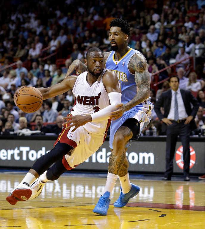 . Miami Heat guard Dwyane Wade (3) drives around Denver Nuggets forward Wilson Chandler (21) during the first half of an NBA basketball game in Miami, Friday, March 14, 2014. The Nuggets won 111-107. (AP Photo/Alan Diaz)