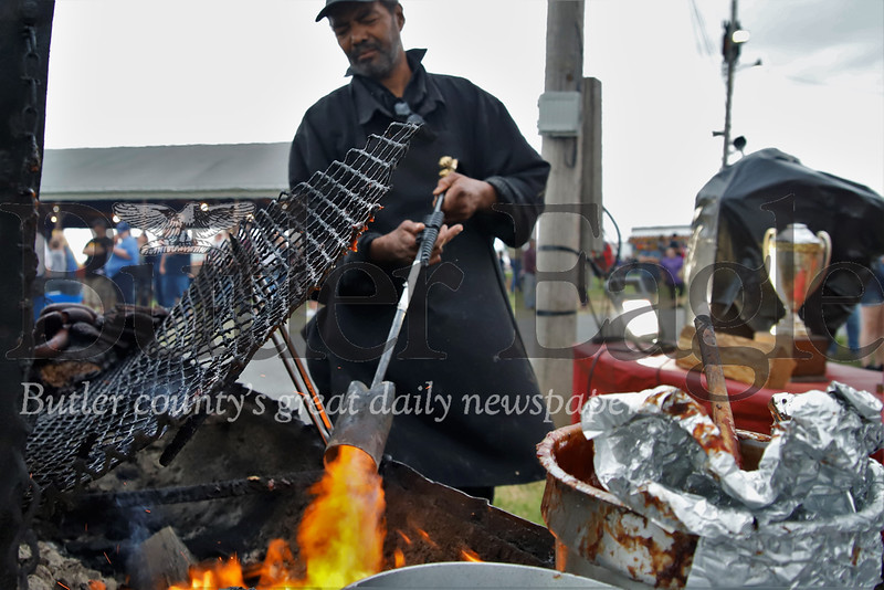 Kevin Williams of Johnson BBQ re-fires the grill with a propane torch at the Butler Rib & Music Festival over the weekend. Seb Foltz/Butler Eagle