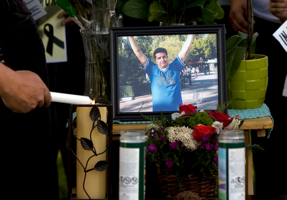 . A mourner lights candles at a makeshift memorial before a news conference in Salt Lake City on Sunday, May 5, 2013, by the family to discuss the death of Ricardo Portillo, who passed away after injuries he sustained after an assault by a soccer player at a soccer game he was refereeing on April 27.  (AP Photo/The Salt Lake Tribune, Kim Raff)