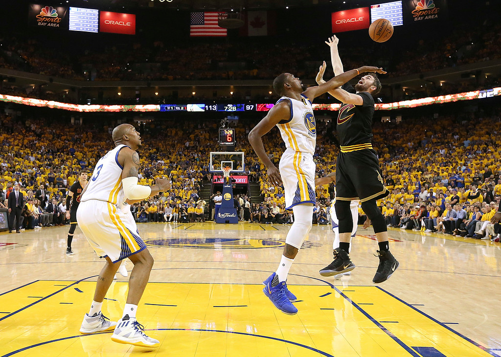 . Golden State Warriors forward Kevin Durant, center, defends a shot by Cleveland Cavaliers forward Kevin Love during the second half of Game 2 of basketball\'s NBA Finals in Oakland, Calif., Sunday, June 4, 2017. (Ezra Shaw/Pool Photo via AP)