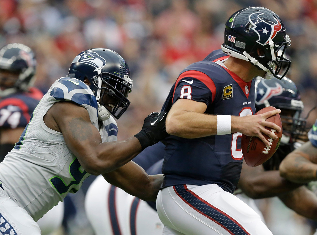 . Seattle Seahawks\' Chris Clemons, left, grabs Houston Texans\' Matt Schaub (8) who looks to pass during the first quarter an NFL football game on Sunday, Sept. 29, 2013, in Houston. (AP Photo/Patric Schneider)