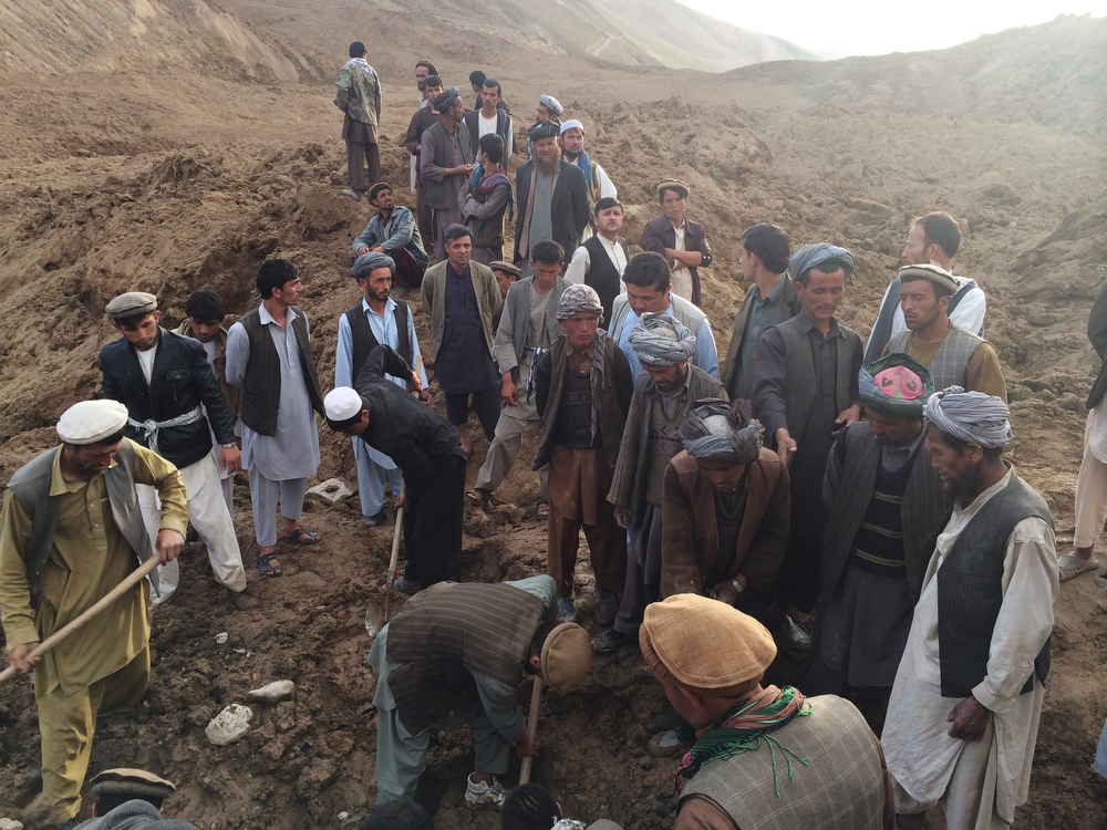 . In this Friday, May 2, 2014 photo provided by Homayoon Rahmani, chief of road reconstruction program in the Afghan Rural and Rehabilitation Development Ministry, Afghans search for survivors buried after a massive landslide in a village in Badakshan province, northeastern Afghanistan. Afghan rescuers and hundreds of volunteers armed with shovels rushed on Saturday to help villagers hit by a massive landslide in the remote northeast a day earlier, officials said, while fears of a new torrent of mud and earth complicated rescue efforts. (AP Photo/Homayoon Rahmani)