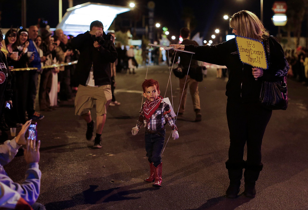 . Shelley Brittell, right, guides her son, Jaden Brittell, 3, down Fremont Street dressed as a Howdy Doody puppet in the fourth annual Las Vegas Halloween Parade, Thursday, Oct. 31, 2013, in Las Vegas. (AP Photo/Julie Jacobson)