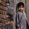 A boy poses against broken wall in a village in Pakistan