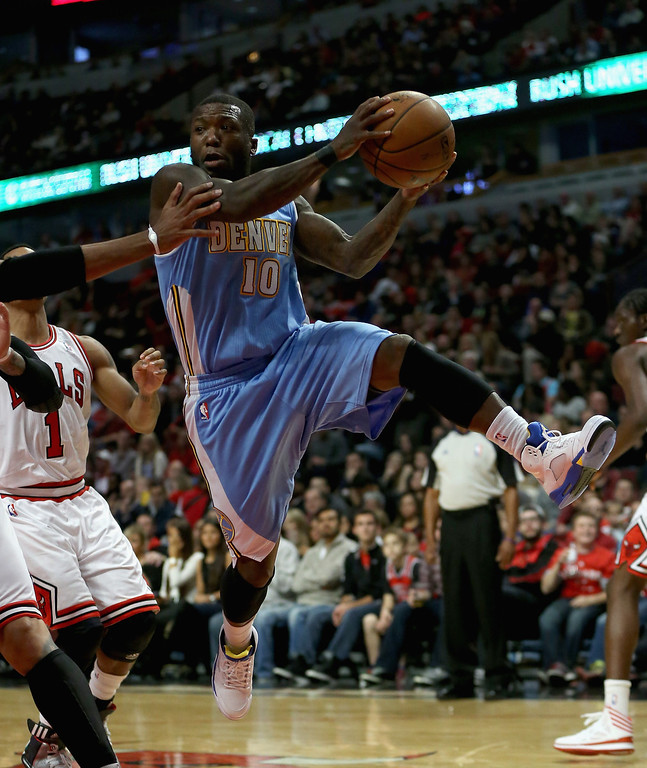 . Nate Robinson #10 of the Denver Nuggets leaps to pass against the Chicago Bulls during a preseason game at the United Center on October 25, 2013 in Chicago, Illinois. (Photo by Jonathan Daniel/Getty Images)