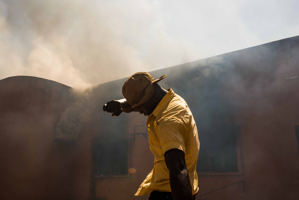 . A protestor near the burning parliament building in Burkina Faso as people protest  against their longtime president  Blaise Compaore  who is  seeking  another term in Ouagadougou, Burkina Faso, Thursday, Oct. 30, 2014. (AP Photo/Theo Renaut)