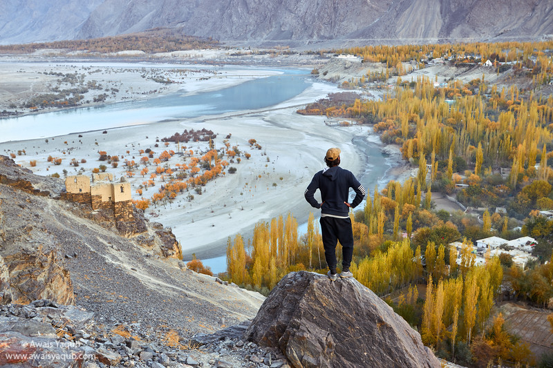 Man overlooks Skardu City dranched in autumnal colors in November.