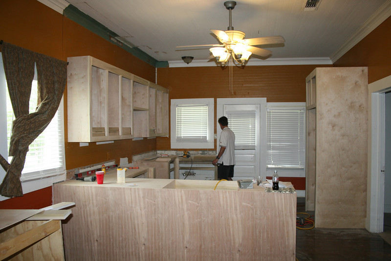 new kitchen cabinets and refrigerator nook being built on site / custom