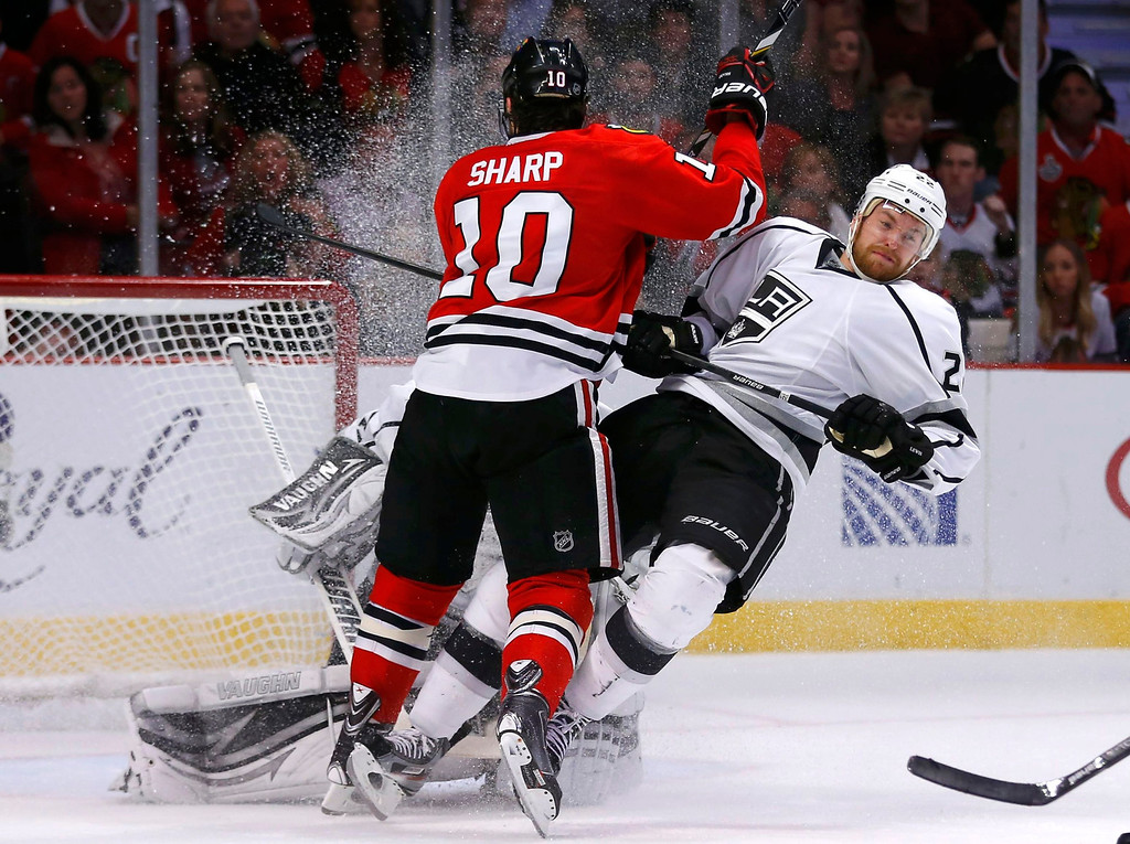. Chicago Blackhawks\' Patrick Sharp (10) checks Los Angeles Kings\' Trevor Lewis during the second period in Game 5 of their NHL Western Conference final hockey playoff series in Chicago, Illinois, June 8, 2013. REUTERS/Jeff Haynes