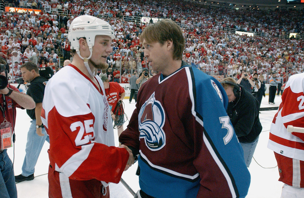 . Goaltender Patrick Roy #33 of the Colorado Avalanche congratulates right wing Darren McCarty #25 of the Detroit Red Wings after game seven of the Western Conference finals in the Stanley Cup playoffs at the Joe Louis Arena in Detroit, Michigan on May 31, 2002. The Red Wings won 7-0 to take the series 4-3. (Photo by Dave Sandford/Getty Images/NHLI)