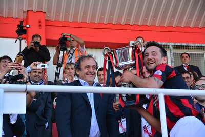 Lincoln Red Imps captain embraces the Rock Cup after it was presented to him by UEFA President Michel Platini.