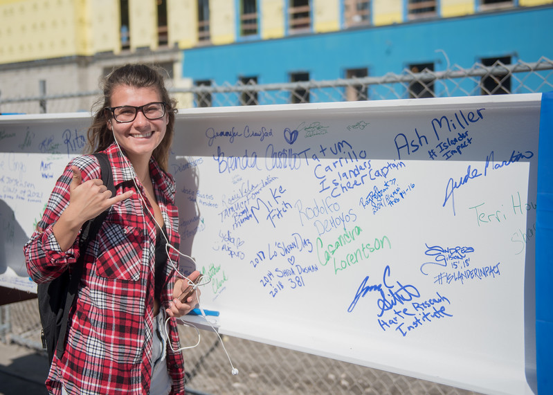 "Lydia Aispuro poses for a photo after signing a steel beam which will be used during the Topping Out Ceremony for Tidal Hall.   Click on the link to read about the ""Topping Out"" Ceremony: http://bit.ly/2hfLRho"