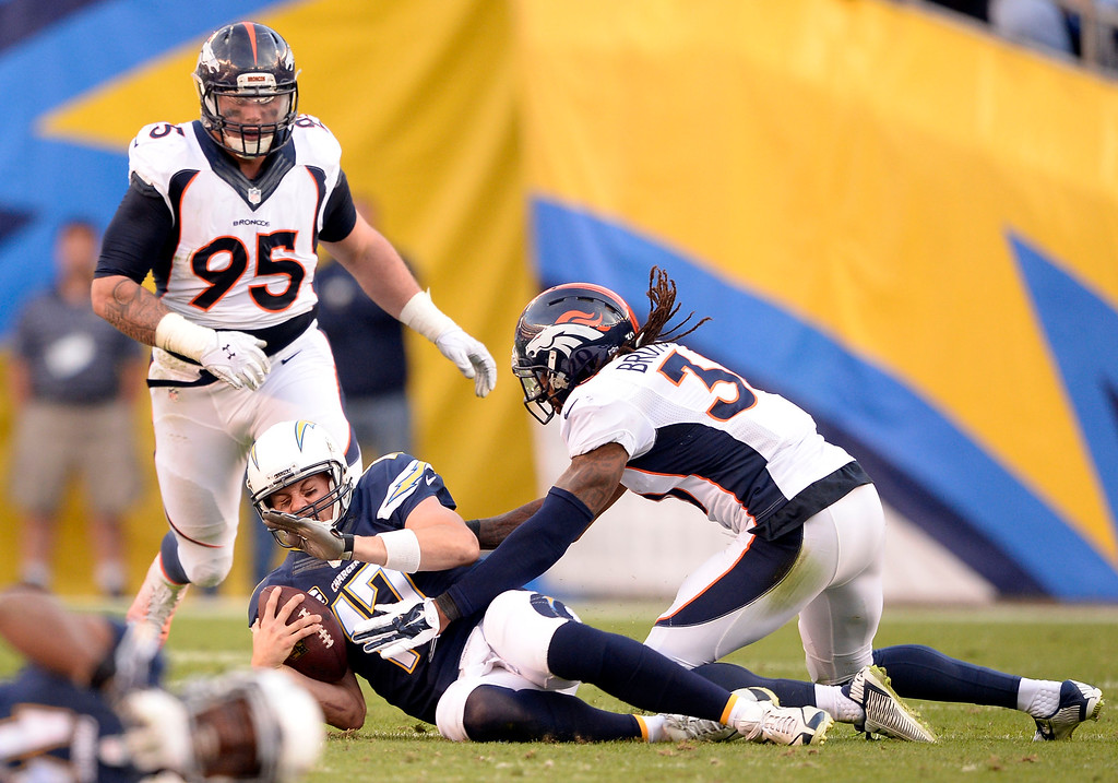 . SAN DIEGO, CA - DECEMBER 14: San Diego Chargers quarterback Philip Rivers (17) slides after picking up a few yards before Denver Broncos strong safety David Bruton (30) can hit him December 14, 2014 at Qualcomm Stadium (Photo By John Leyba/The Denver Post)