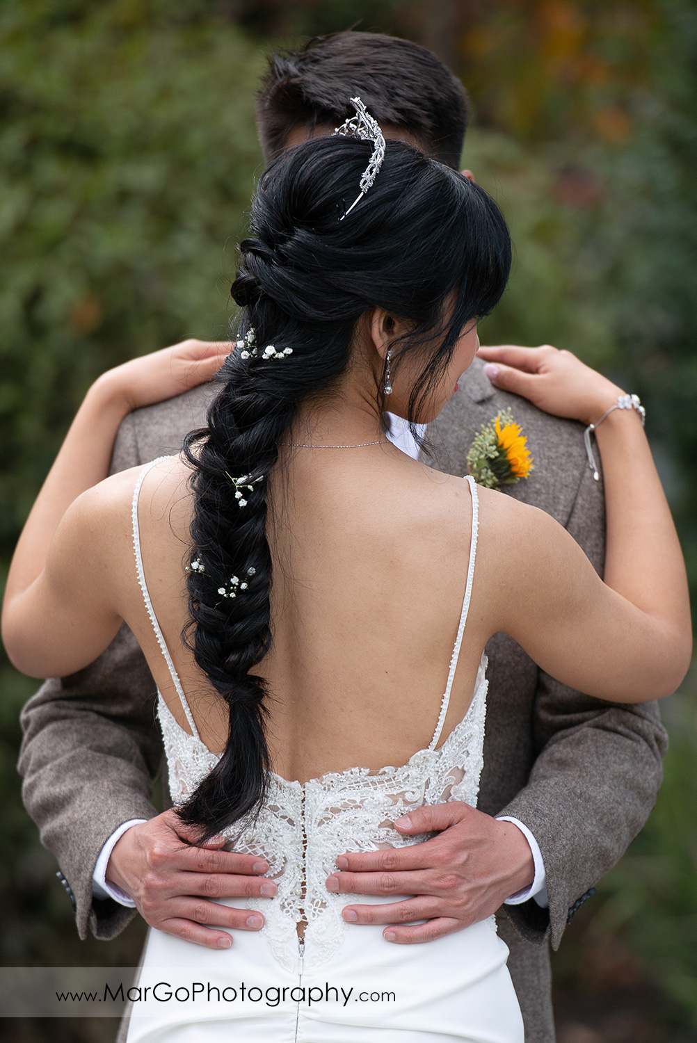groom holding hands on bide's waist at Long Branch Saloon & Farms in Half Moon Bay