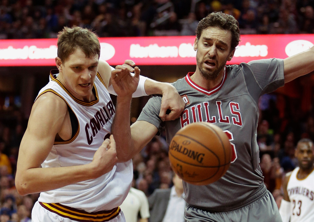 . Cleveland Cavaliers\' Timofey Mozgov, left, from Russia, and Chicago Bulls� Pau Gasol, from Spain, battle for a loose ball in the first half of an NBA basketball game Saturday, Jan. 23, 2016, in Cleveland. (AP Photo/Tony Dejak)