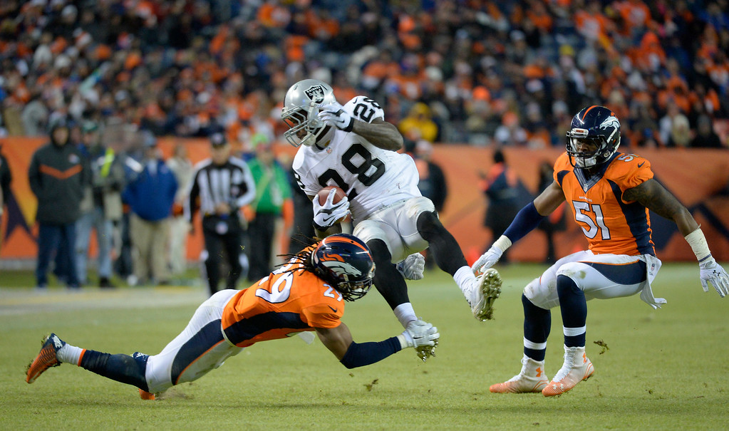 . DENVER, CO - DECEMBER 28: Latavius Murray (28) of the Oakland Raiders gets it by Bradley Roby (29) of the Denver Broncos during the fourth quarter. The Denver Broncos played the Oakland Raiders at Sports Authority Field at Mile High in Denver on December, 28 2014. (Photo by Joe Amon/The Denver Post)