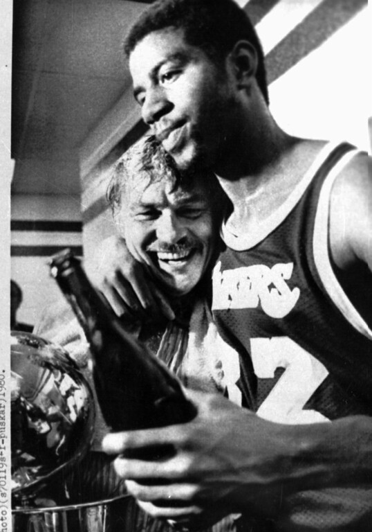 ". Los Angeles Lakers Earvin ""Magic\"" Johnson hugs team owner Jerry Buss in the locker room after they won the 1980 NBA championship from the 76ers in Philadelphia May 17, 1980. They drank champagne and admired their trophy following the 123-107 win in the sixth game of the series. (AP photo/Gene Pushkar)"