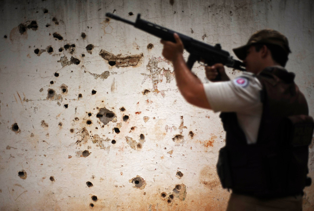 """. Police patrol past the \""""rifle wall\"""" pockmarked by bullets from many shootouts between drug gangs and police, in the Nordeste de Amaralina slum complex in Salvador, Bahia State, March 28, 2013. One of Brazil\'s main tourist destinations and a 2014 World Cup host city, Salvador suffers from an unprecedented wave of violence with an increase of over 250% in the murder rate, according to the Brazilian Center for Latin American Studies (CEBELA). Picture taken March 28, 2013.  REUTERS/Lunae Parracho"""