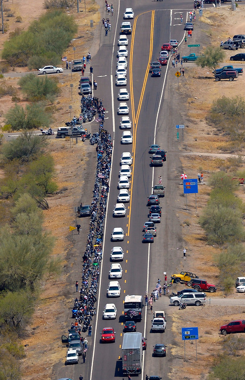 . A procession of 19 hearses for the 19 fallen Arizona firefighters drives through the desert, Sunday, July 7, 2013, near Wickenburg, Ariz, The elite crew of firefighters were overtaken by the out-of-control blaze as they tried to protect themselves from the flames under fire-resistant shields last Sunday.  (AP Photo/Mark J. Terrill)