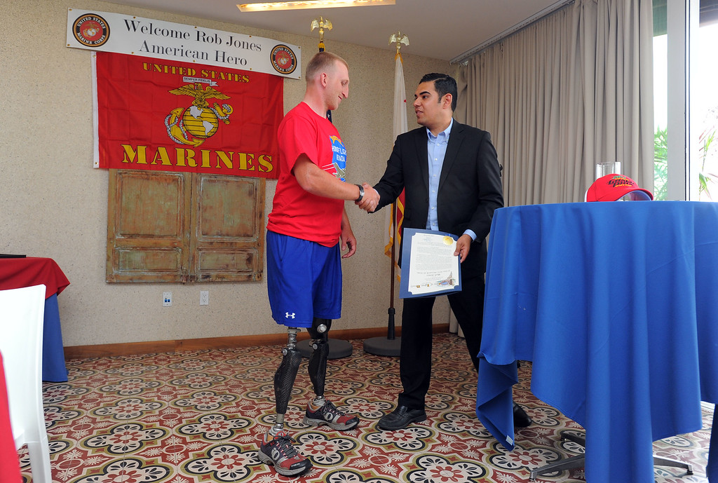. Double amputee marine veteran Rob Jones is presented a certificate from the city from Long Beach vice mayor Robert Garcia at a reception at the Hotel Maya in Long Beach, CA on Thursday, April 10, 2014. Jones began riding his bicycle across the country in Maine in October and will his fundraising journey Saturday at Camp Pendleton. (Photo by Scott Varley, Daily Breeze)