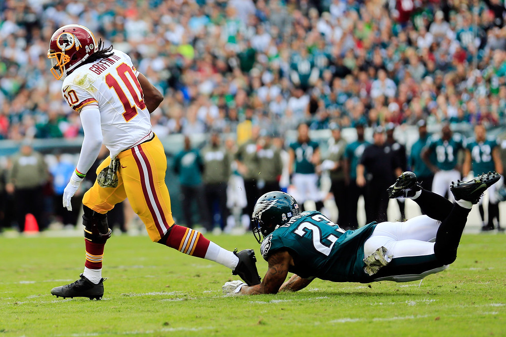 . Quarterback Robert Griffin III #10 of the Washington Redskins eludes the tackle of free safety Patrick Chung #23 of the Philadelphia Eagles during the first quarter at Lincoln Financial Field on November 17, 2013 in Philadelphia, Pennsylvania.  (Photo by Rob Carr/Getty Images)