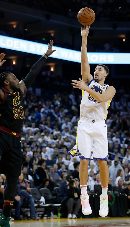 . Golden State Warriors guard Klay Thompson (11) shoots a 3-point shot over Cleveland Cavaliers forward Jae Crowder (99) during the second half of an NBA basketball game in Oakland, Calif., Monday, Dec. 25, 2017. The Warriors won 99-92. (AP Photo/Tony Avelar)