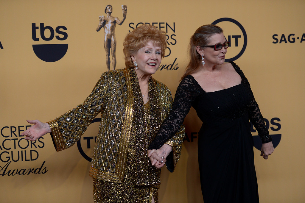". Debbie Reynolds and Carrie Fisher pose backstage at the 21st Annual Screen Actors Guild Awards at the Shrine Auditorium in Los Angeles, California on Sunday January 25, 2014. Reynolds was honored with the Life Achievement Award. Reynolds, star of the 1952 classic ""Singin\' in the Rain\"" died Wednesday, Dec. 28, 2016. She was 84. Her daughter, Fisher, died Dec. 27, 2016. (Photos by Andy Holzman, Los Angeles Daily News/SCNG)"