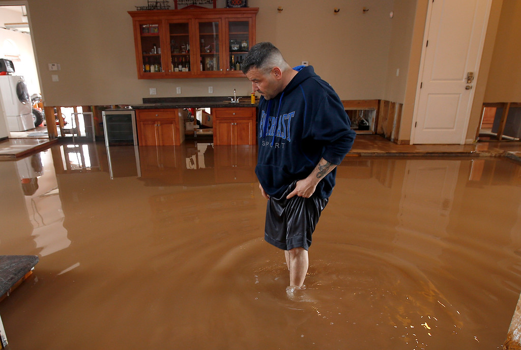 . A dismayed Nick Kriaris wades through his flooded home after heavy rains caused severe flash flooding Monday, Sept. 8, 2014, in Phoenix.  His home has flooded three times in the past month, and he was just fixing the damage in his home from the previous two monsoon storm hit. The Monday morning storm set an all-time record for rainfall in Phoenix in a single day. (AP Photo/Ross D. Franklin)