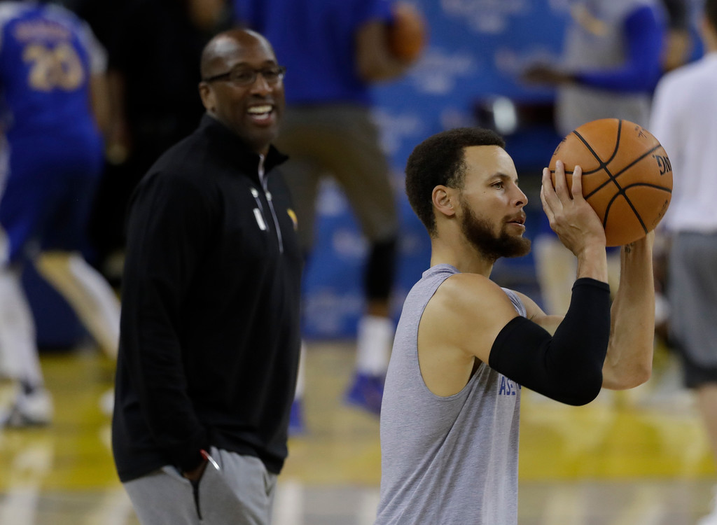 . Golden State Warriors\' Stephen Curry, right, shoots as interim head coach Mike Brown watches during an NBA basketball practice, Wednesday, May 31, 2017, in Oakland, Calif. The Golden State Warriors face the Cleveland Cavaliers in Game 1 of the NBA Finals on Thursday in Oakland. (AP Photo/Marcio Jose Sanchez)