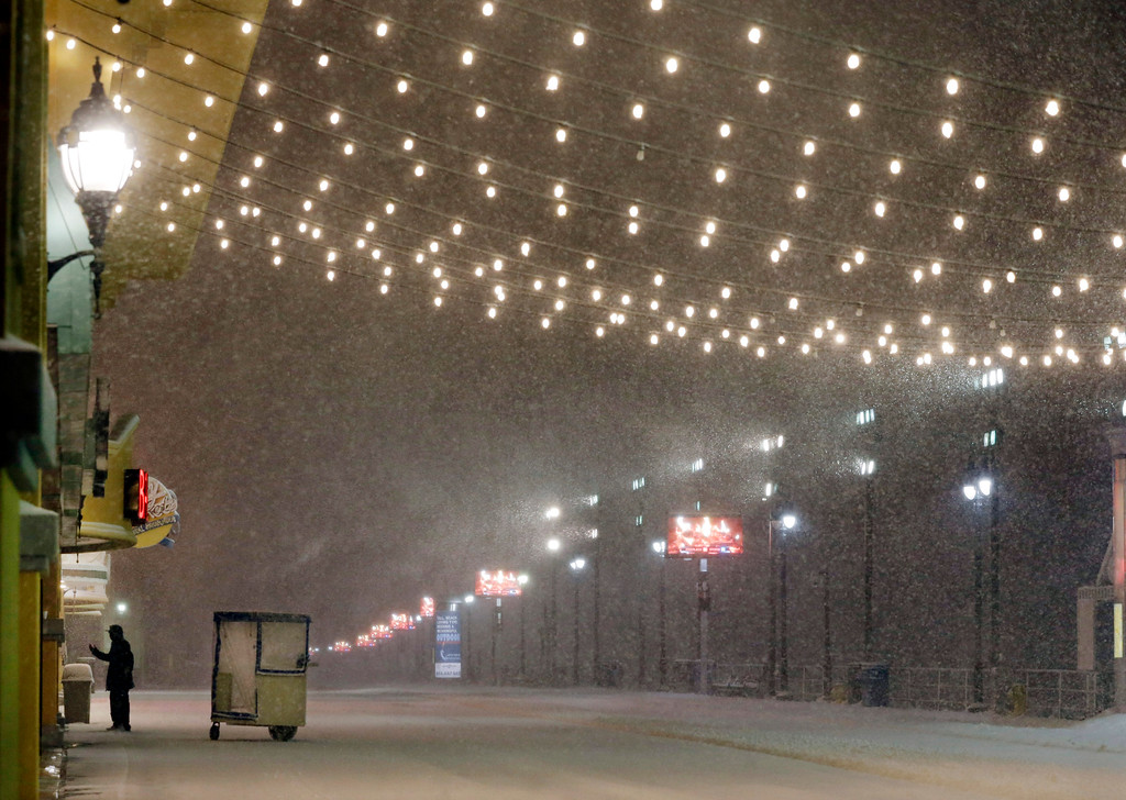 . A man stands near his Push cart during a snowstorm early Saturday, Jan. 23, 2016, on the Atlantic City Boardwalk. Most of the state was facing a blizzard warning from Friday evening until Sunday that called for up to 24 inches of snow, with the deepest accumulations in the central part of the state. (AP Photo/Mel Evans)