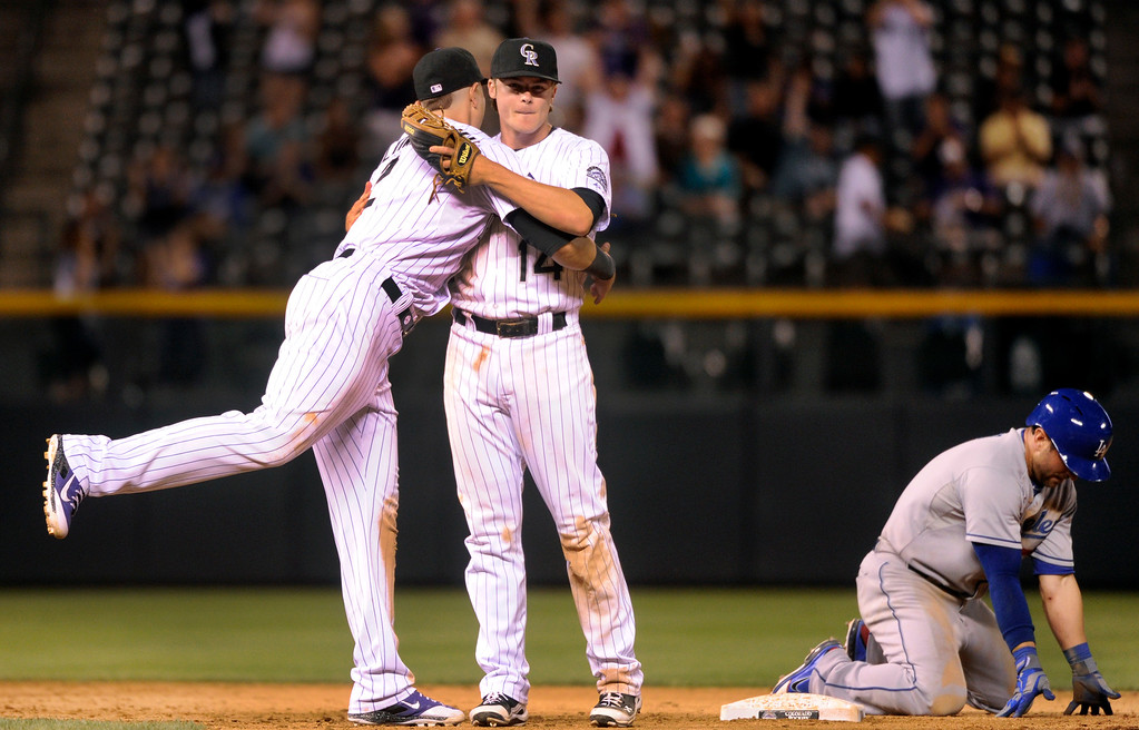 . DENVER, CO. - SEPTEMBER 4: Colorado infielders Troy Tulowitzki and Josh Rutledge celebrate the final out with LA baserunner Nick Punto at second base. The Colorado Rockies defeated the Los Angeles Dodgers 7-5 at Coors Field Wednesday night, September 4, 2013.  Photo By Karl Gehring/The Denver Post