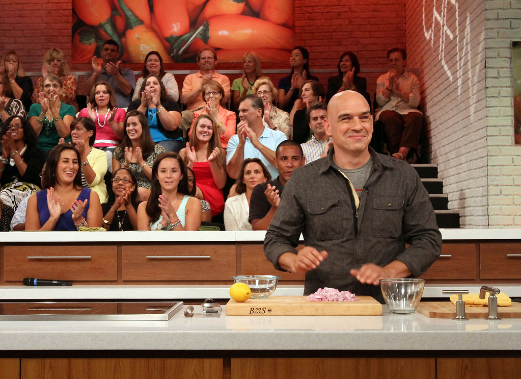 ". FILE - In this Aug. 26, 2011, file photo, audience members applaud while Iron Chef Michael Symon, co-host of ABC\'s ""The Chew,\"" foreground, starts a segment during a rehearsal for the show in New York. Celebrity chef and cookbook author Symon said a fire Sunday, Jan. 10, 2016, has significantly damaged one of his first restaurants in his hometown of Cleveland. (AP Photo/Tina Fineberg, File)"