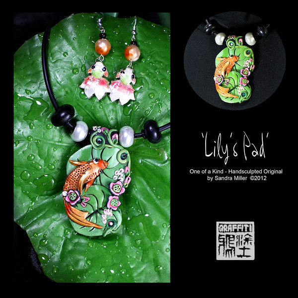 """LILY'S PAD KOI NECKLACE AND EARRING SET  Mz Lily the Koi wants to invite you over to her 'pad' for some green tea and mooncakes!  Her little cloisonne earring friends """"Bud"""" and """"Blossom"""" said they will bring fortune cookies!  This elegant koi has an iridescent finish and is surrounded by hand applied floral elements all the way over the top of the bail as well.  2 large pearlized glass beads flank the pendant with genuine Swarovski crystals studding the lilypads.  The earrings feature vintage lucite swirl beads from an old estate sale bracelet I rescued!  PENDANT MEASURES   2 1/2  x 1 1/2""""   Neoprene cord is finished at the back with chain and adjusts from 16-20"""" long."""