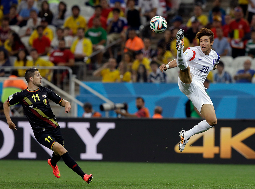 . Belgium\'s Kevin Mirallas watches as South Korea\'s Hong Jeong-ho leaps to clear the ball during the group H World Cup soccer match between South Korea and Belgium at the Itaquerao Stadium in Sao Paulo, Brazil, Thursday, June 26, 2014. (AP Photo/Thanassis Stavrakis)