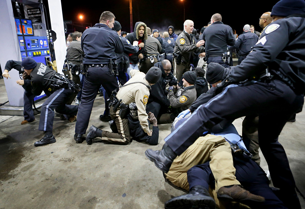 . Police try to control a crowd Wednesday, Dec. 24, 2014, on the lot of a gas station following a shooting Tuesday in Berkeley, Mo. St. Louis County police say a man who pulled a gun and pointed it at an officer has been killed. (AP Photo/St. Louis Post-Dispatch, David Carson)
